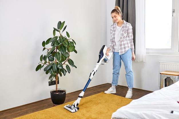 Donna in abbigliamento casual che pulisce con l'aspirapolvere il tappeto giallo che riordina il concetto di pulizia della casa del soggiorno moderno bianco