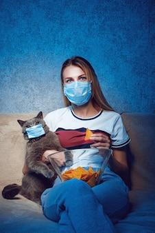 La donna e il gatto sul divano davanti alla tv indossano entrambi delle maschere protettive