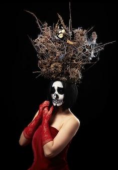 Una donna di aspetto caucasico con trucco scheletrico sta in un vestito rosso con una grande corona di rami secchi