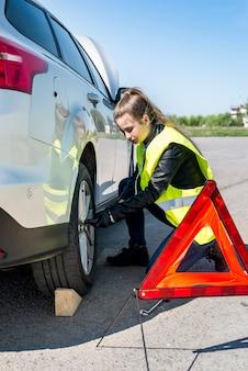 Donna che cambia la ruota danneggiata di un'auto