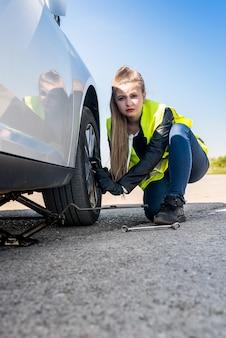 Donna che cambia ruota danneggiata e che la fissa