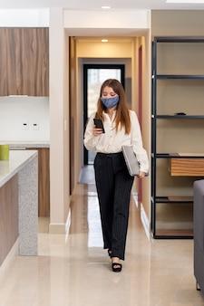 Donna che controlla il cellulare mentre esce di casa per andare al lavoro donna che esce di casa per andare al lavoro