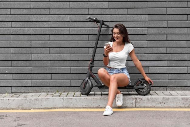 Donna che controlla il suo smartphone mentre è seduto su uno scooter elettrico