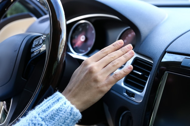 Donna che controlla il funzionamento del condizionatore d'aria in auto