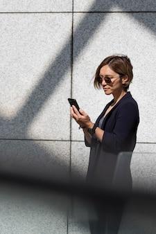 Donna che controlla smartphone colpo medio