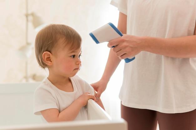 Donna che controlla la temperatura del bambino
