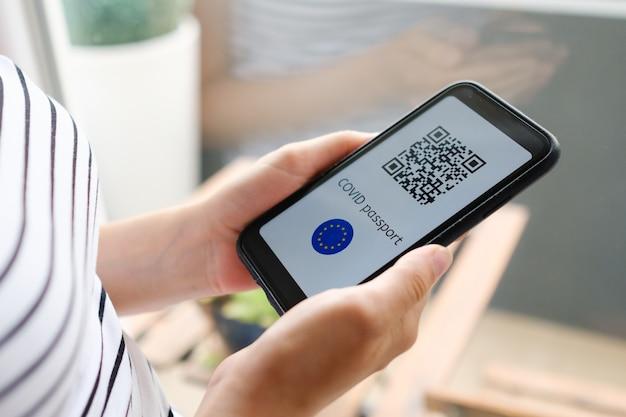 La donna controlla la sua domanda di pass covid o il passaporto sanitario digitale con codice qr e unione europea