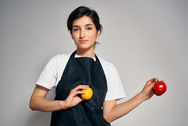 Cuoco unico della donna in vitamine dell'alimento sano delle verdure del grembiule nero