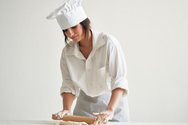 Chef donna stendere la pasta da forno per la cottura. foto di alta qualità
