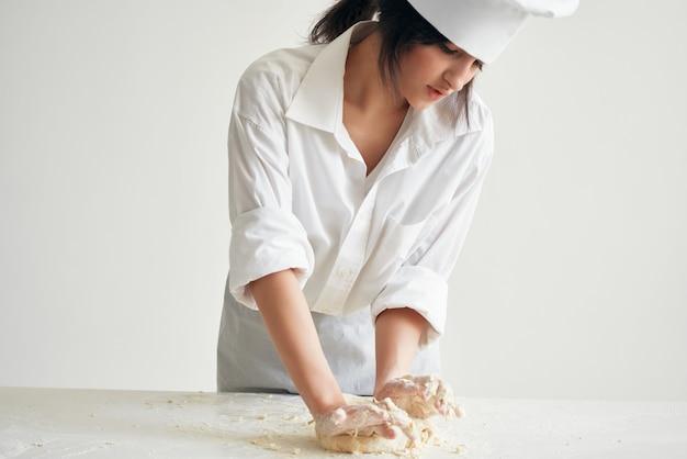 La chef donna stende l'impasto per la cottura del forno