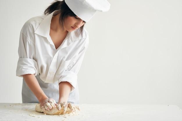 La chef donna stende la pasta per cucinare la pasticceria