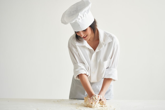 Donna in uniforme da chef panettiere che arrotola la pasta lavorata in cucina