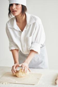 Donna in chef uniformi prodotti di farina che rotolano i compiti dell'impasto