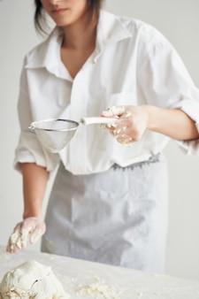 La donna in uniforme da chef in cucina stende l'impasto per cucinare il cibo da forno