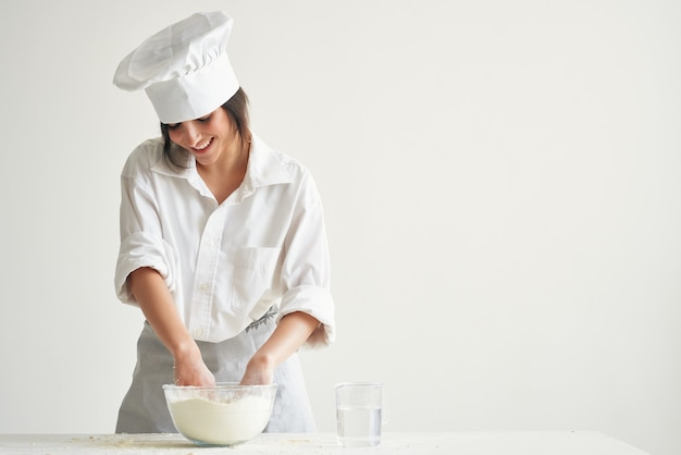 Donna in uniforme da chef che impasta la pasta di cipolla da cucina da forno che cucina pasticceria