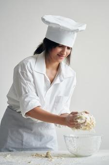 La donna in uniforme da chef impasta la pasta sul fondo della luce della farina della tavola