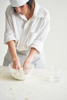 La donna in uniforme da chef setaccia la pasta di farina lavorando in cucina