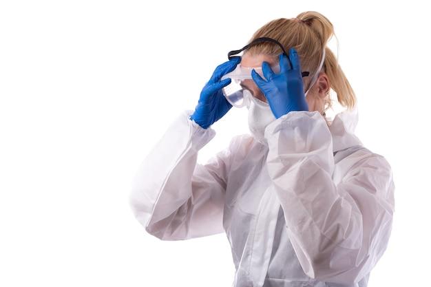 Una donna in una tuta di protezione chimica indossa occhiali e attrezzatura normale. isolato su sfondo bianco.
