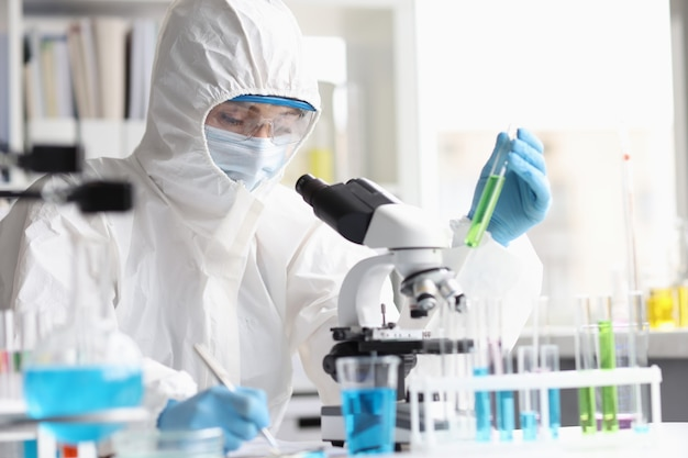 Il chimico della donna in tuta protettiva conduce ricerche di laboratorio sulla scoperta di nuovi liquidi verdi