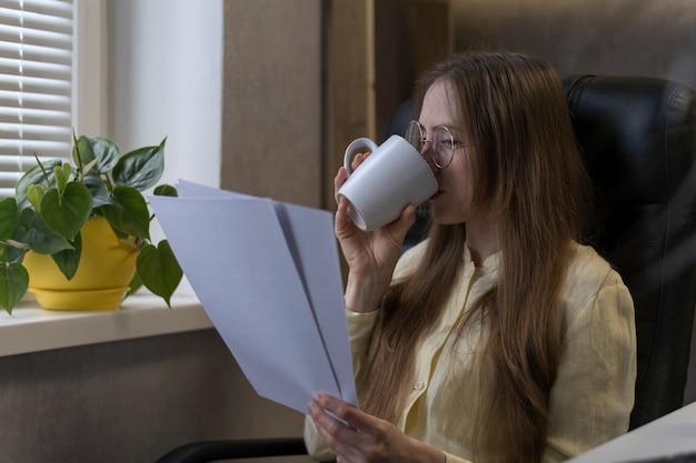 Il capo donna beve caffè e legge il contratto o il rapporto. il direttore lavora durante l'ora di pranzo.