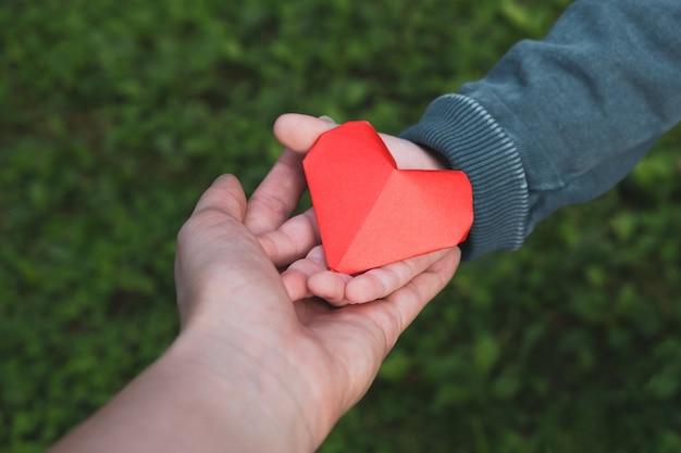 Mani del bambino e della donna che tengono il cuore. salute, amore, concetto di giorno di madri