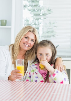 Donna e bambino seduto al tavolo della cucina in possesso di un bicchiere di succo