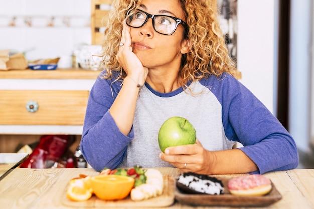 La donna sceglie la mela o la ciambella - dieta e buona nutrizione stile di vita, frutta e ciambella sul tavolo - indoor a casa