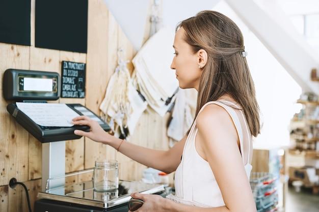 La donna sceglie e acquista prodotti in un negozio a rifiuti zero pesando merci secche in un negozio di alimentari senza plastica plastic Foto Premium