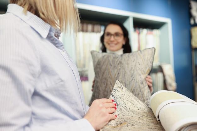 La donna sceglie il tessuto per cucire i cuscini selezione delle soluzioni di colore nel concetto interno