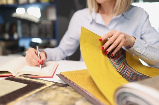 La donna sceglie il tessuto con motivo per tappezzeria all'interno del concetto di catalogo di tessuti del negozio