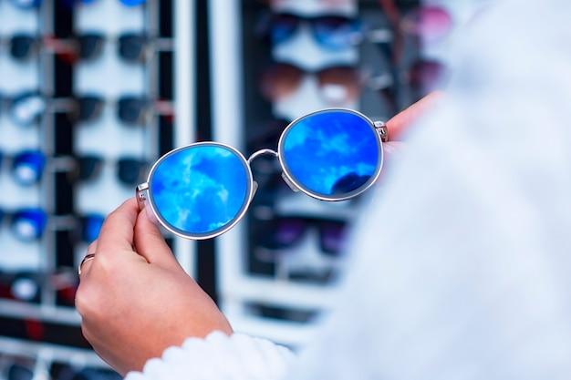 Una donna sceglie occhiali da sole protettivi sullo sfondo di una vetrina con gli occhiali.