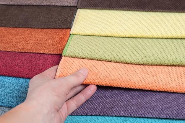 La donna sceglie i campioni di tessuto colorato sul primo piano del tavolo