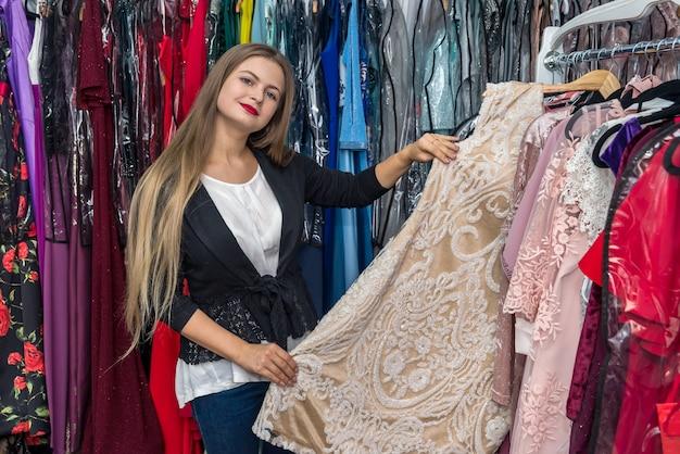 Donna che sceglie bellissimo indumento da sera nel negozio di vestiti