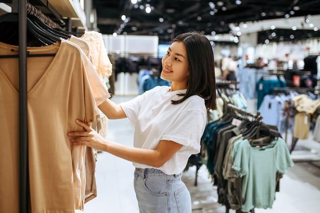 Donna che sceglie i vestiti nel negozio di abbigliamento. persona di sesso femminile che acquista in boutique di moda, shopaholic, acquirente alla ricerca di indumento