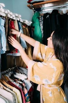 Donna che sceglie i vestiti in un guardaroba