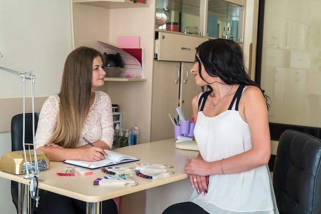 Donna che sceglie il colore dello smalto per unghie nel salone di bellezza