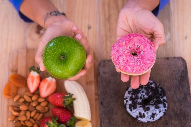 Donna che sceglie mela verde o dunt - concetto di stile di vita sano e salutare - sul tavolo, ci sono una ciambella e alcuni frutti