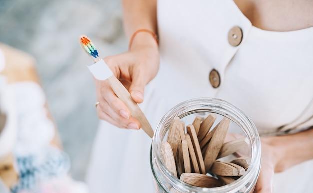 Donna che sceglie spazzolini da denti ecologici in bambù in legno in un negozio a zero rifiuti
