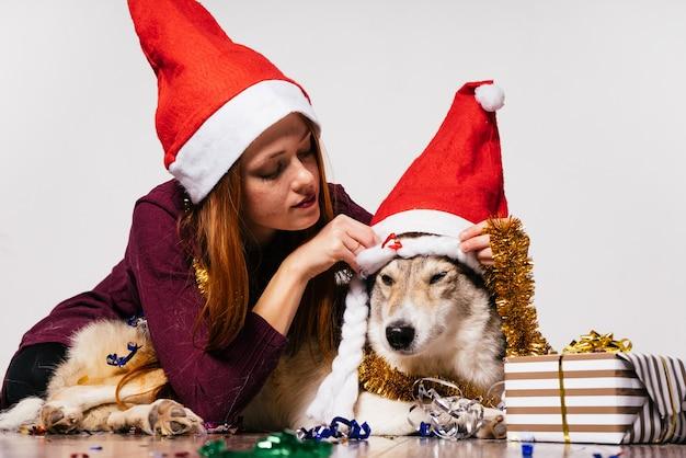Donna con un cappello di natale che abbraccia un cane