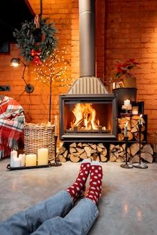 Donna in calze di natale davanti al caminetto a casa. il concetto di comfort durante le vacanze invernali e di capodanno