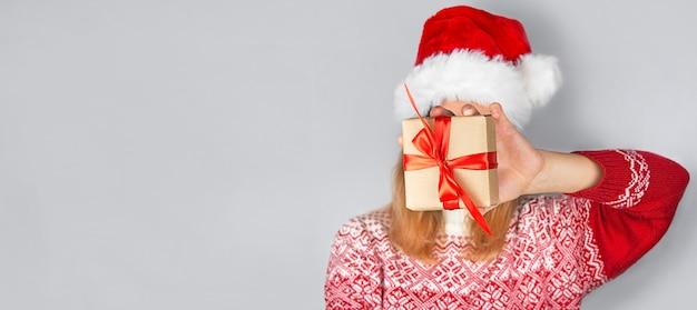 Una donna con un maglione natalizio tiene in mano una confezione regalo. regali di natale. sfondo di natale. bandiera. copia spazio.