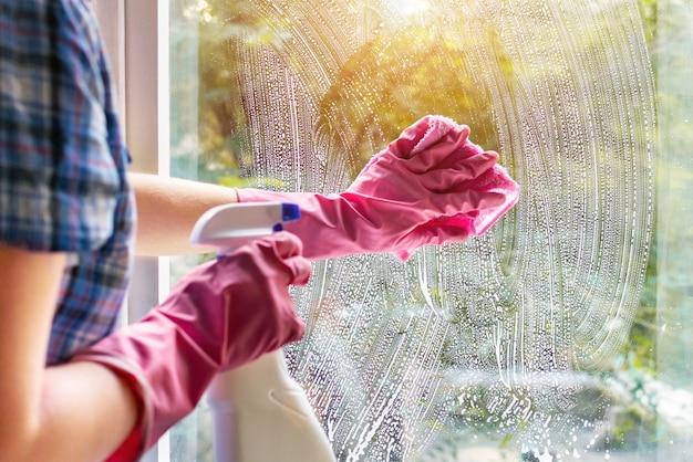 Una donna pulisce il vetro di una finestra con uno straccio e una schiuma di sapone. pulizia con un detergente. mani in guanti protettivi rosa che lavano il vetro sulle finestre della casa con un flacone spray, concetto di routine domestica.