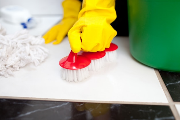 Donna che pulisce il pavimento di un bagno