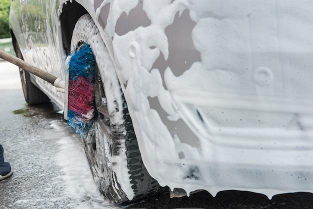 Donna che pulisce la ruota dell'auto con spazzola e schiuma. concetto di pulizia