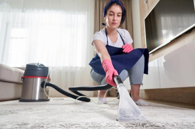 Donna che pulisce il tappeto nel soggiorno utilizzando l'aspirapolvere a casa. concetto di servizio di pulizia