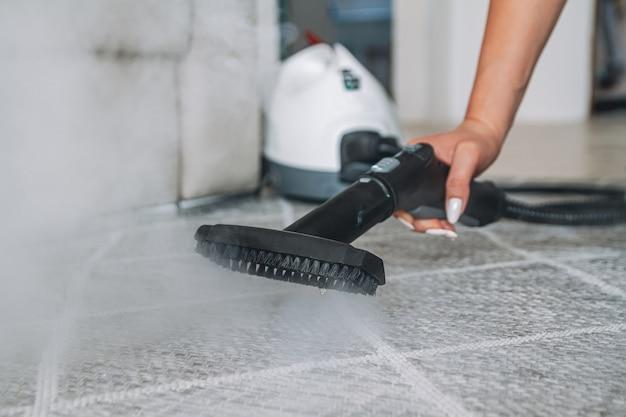 Tappeto di pulizia della donna con un pulitore a vapore