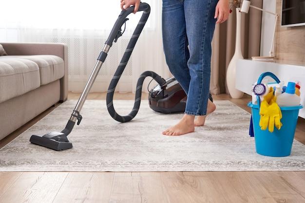Donna che pulisce il tappeto con l'aspirapolvere nel soggiorno moderno