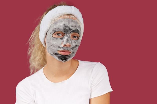 Donna che pulisce la pelle del viso si diverte con la schiuma detergente a bolle