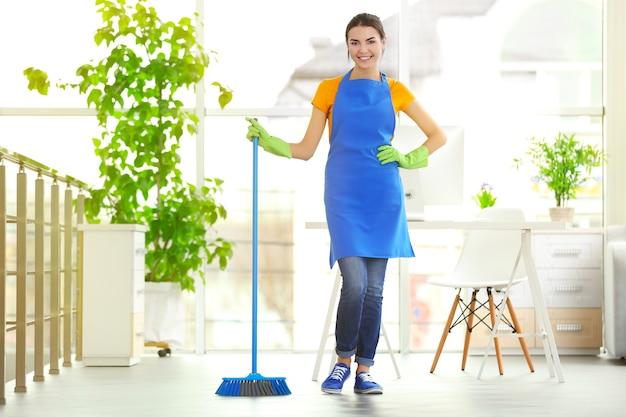 Donna che pulisce il pavimento con la scopa al chiuso