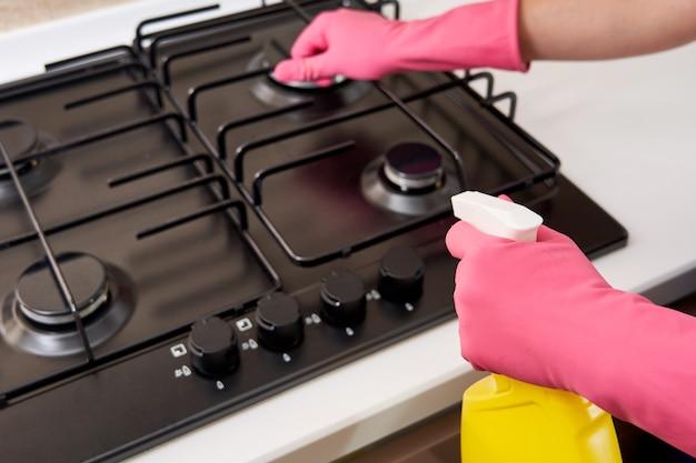 Donna che pulisce un fornello a gas con utensili da cucina